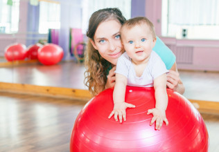 Mother with happy baby doing exercises with gymnastic ball