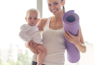 Portrait of beautiful young mom in sports wear holding her charming little baby and yoga mat, looking at camera and smiling while standing against window